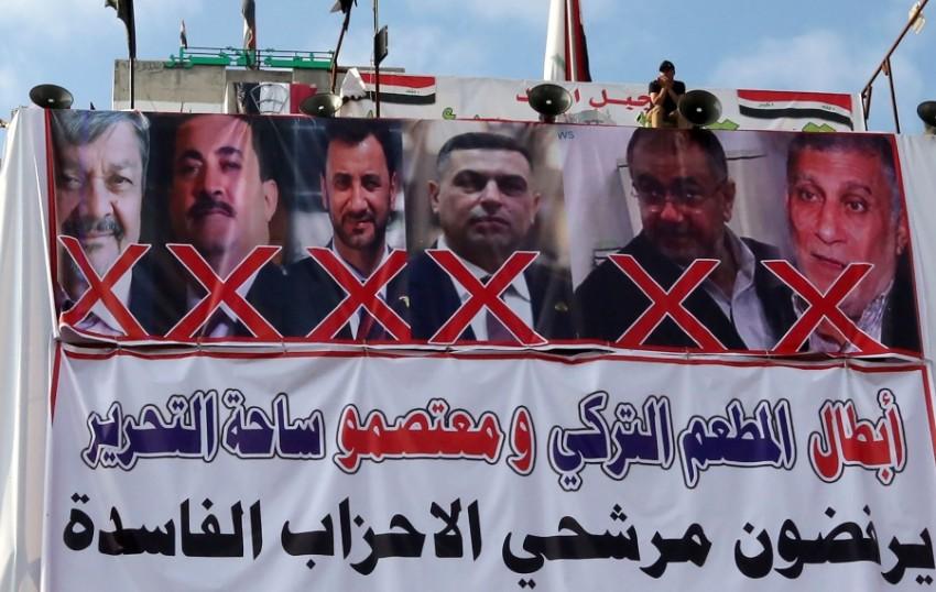 ملصق رفعه المحتجون في ساحة التحرير لرفض أسماء مرشحة لتولي الحكومة. (أ ف ب)