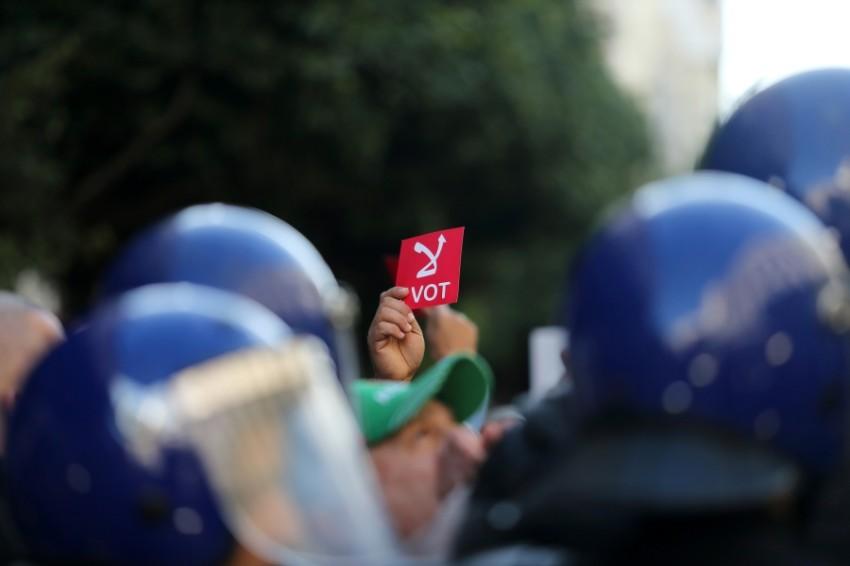 متظاهر يشير ببطاقة لرفض التصويت في الانتخابات الرئاسية بالجزائر العاصمة. (رويترز)