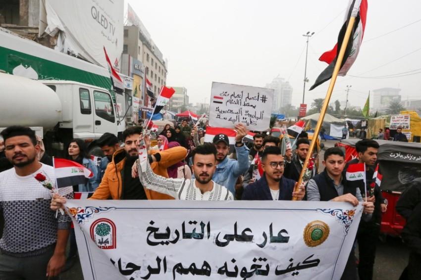 متظاهرون عراقيون في ميدان التحرير بالعاصمة بغداد. (أ ف ب)