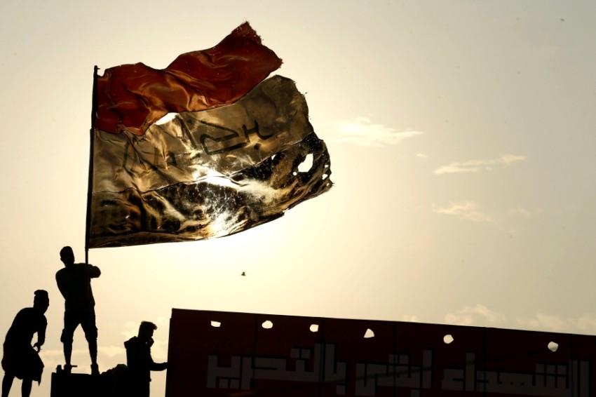 متظاهر يرفع علم العراق في بغداد. (رويترز)