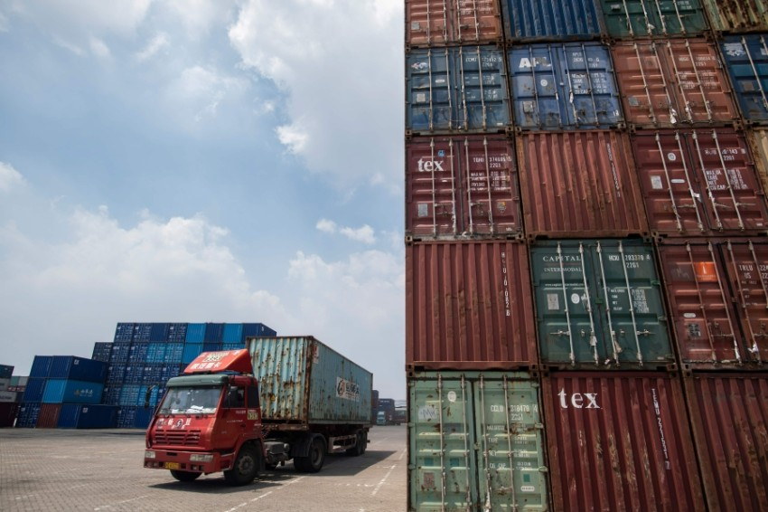 (FILES) This file picture taken on August 7, 2018 shows a truck transporting a container next to stacked containers at a port in Zhangjiagang in China's eastern Jiangsu province. - China welcomed on September 13, 2018 a US offer to hold fresh trade talks, adding that the two are discussing the details and providing some hope the world's top economies could step back from the brink of an all-out trade war. (Photo by JOHANNES EISELE / AFP), مخازن للتبادل التجاري