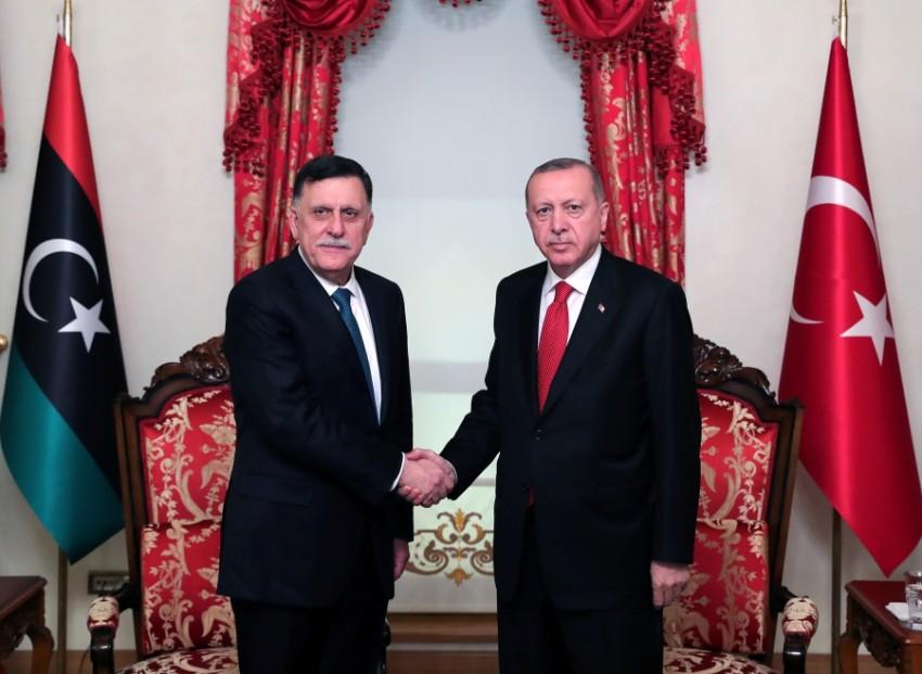 الرئيس التركي رجب طيب أردوغان، مصافحاً رئيس حكومة طرابلس فايز السراج في اسطنبول. (رويترز)