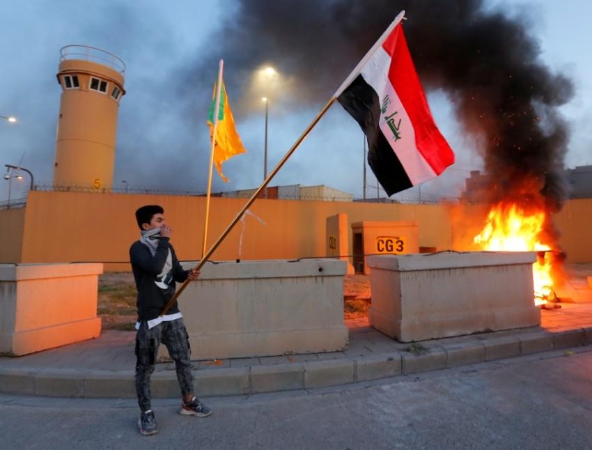 محتج يرفع علم العراق أمام السفارة الأمريكية في بغداد أمس. (رويترز)