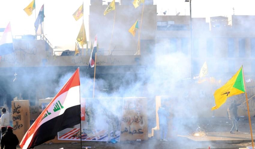 قوات أمريكية تطلق الغاز لتفريق ميليشيات تحاصر سفارة واشنطن اليوم. (رويترز)