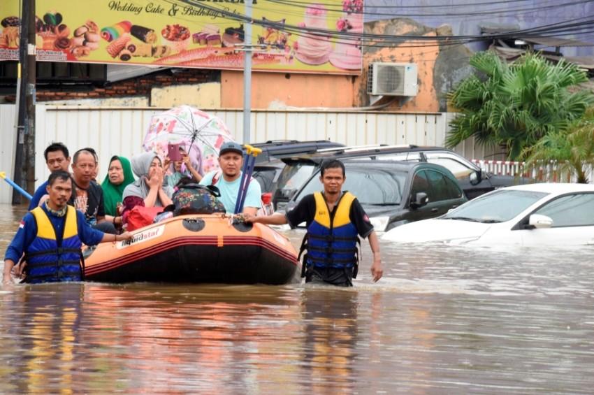 إجلاء أسرة من الفيضانات في العاصمة الإندونيسية جاكرتا اليوم. (رويترز)