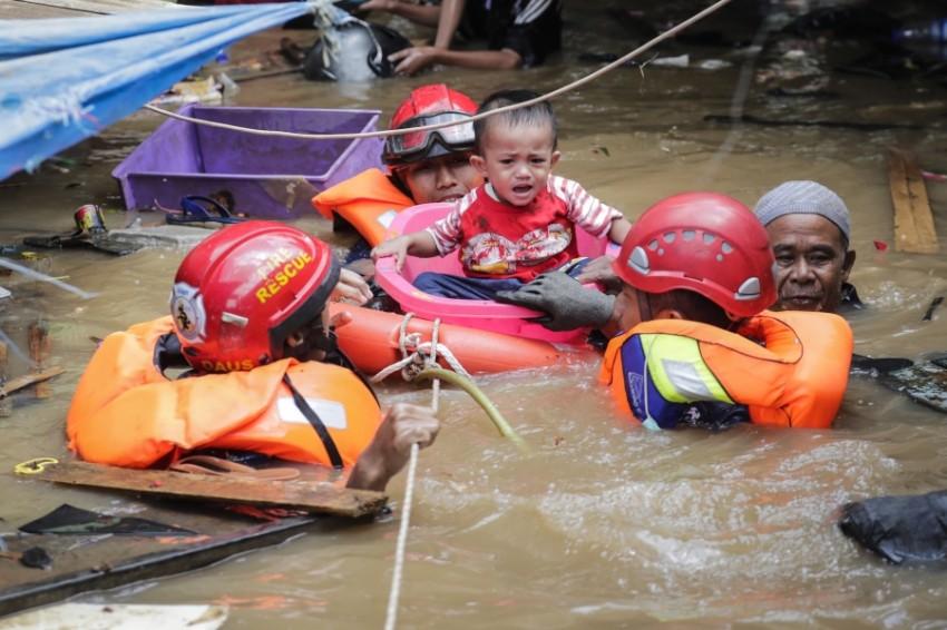 فرق الاغاثة تنقذ طفل من فيضانات جاكرتا(أي بي أيه)