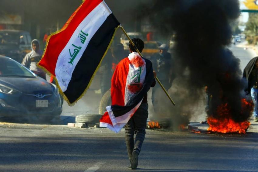 متظاهر يحمل علم العراق خلال احتجاجات في النجف. (رويترز)
