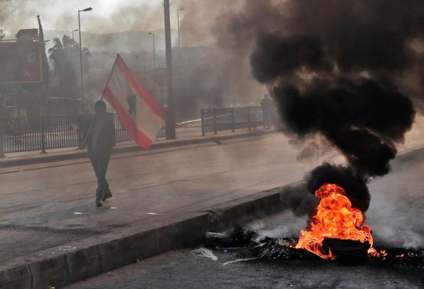متظاهر يحمل العلم اللبناني خلال احتجاجات في بيروت. (أ ف ب)