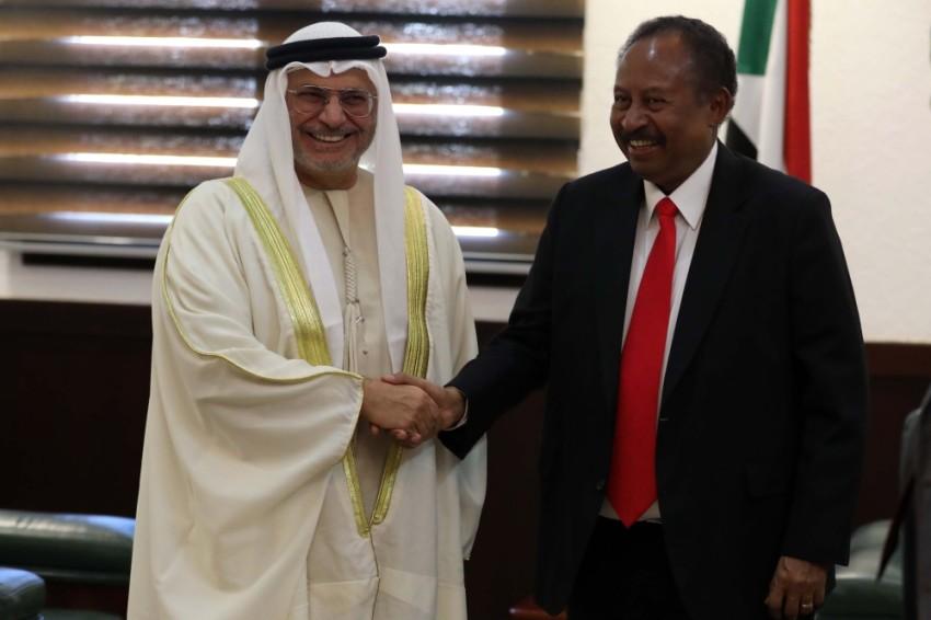 أنور قرقاش مصافحاً عبدالله حمدوك في الخرطوم.