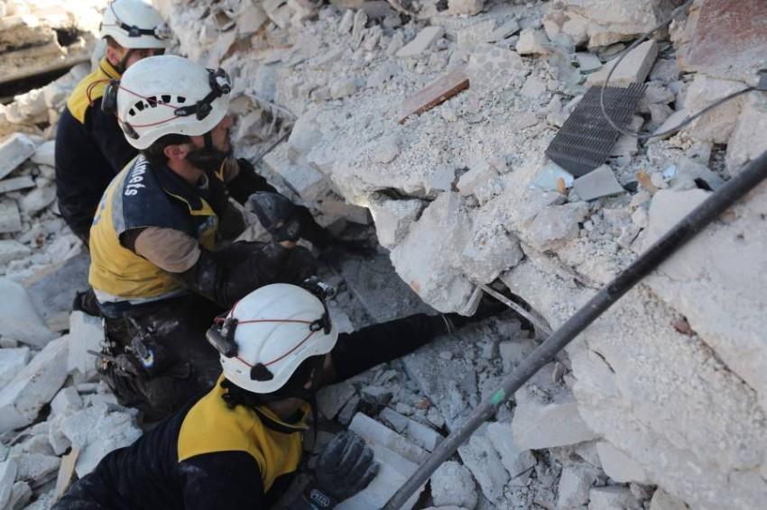 عمال إنقاذ يبحثون عن ضحايا الغارات الجوية على شمال غرب سوريا. (أ ف ب)