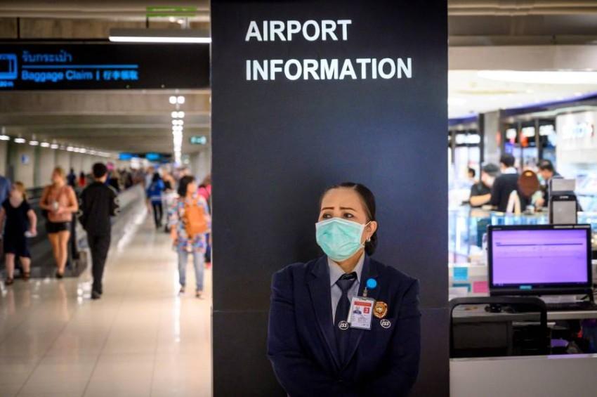 موظفة ترتدي قناعاً واقياً داخل مطار في بانكوك. (أ ف ب)