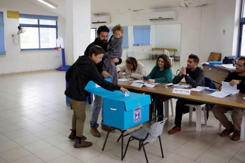 إسرائيلي يصطحب أطفاله للإدلاء بصوته في الانتخابات. (رويترز)