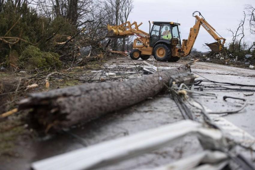 عمال يفتحون الطرقات التي أغلقت جراء الزوابع في ولاية تينيسي الأمريكية. (أ ف ب)