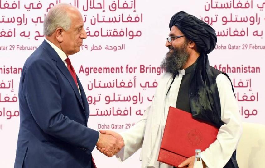 زلماي خليل زاده يصافح المسئول السياسي في طالبان الملا برادار في الدوحة (إي بي أيه)