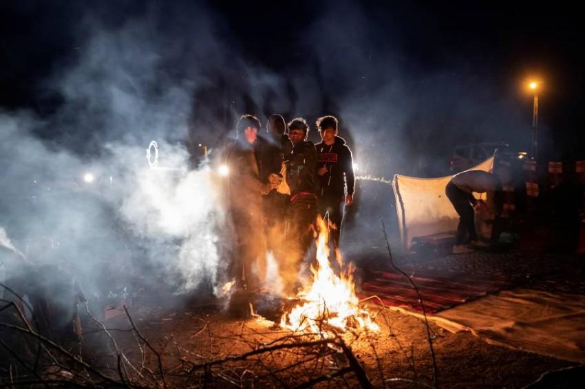 مهاجرون يدفئون أنفسهم قرب الحدود التركية اليونانية. (رويترز)