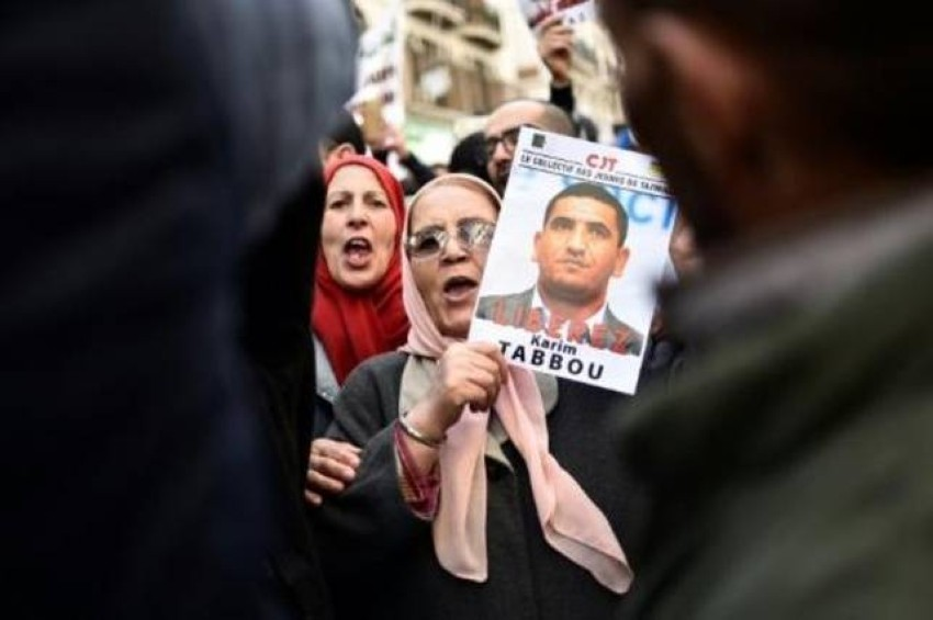 متظاهرون يحملون صورة كريم طابو بالجزائر. (الرؤية)