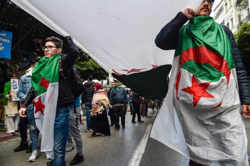 محتجون يتشحون بعلم الجزائر أثناء احتجاجات الحراك. (أ ف ب)