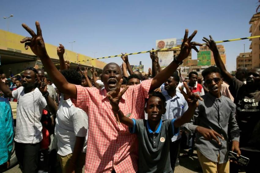 سودانيون يرددون شعارات قرب موقع محاولة اغتيال رئيس الوزراء السوداني في الخرطوم. (رويترز)