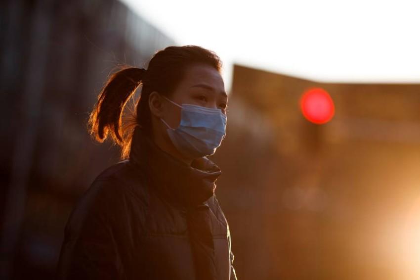 صينية ترتدي قناعاً واقياً في بكين. (رويترز)