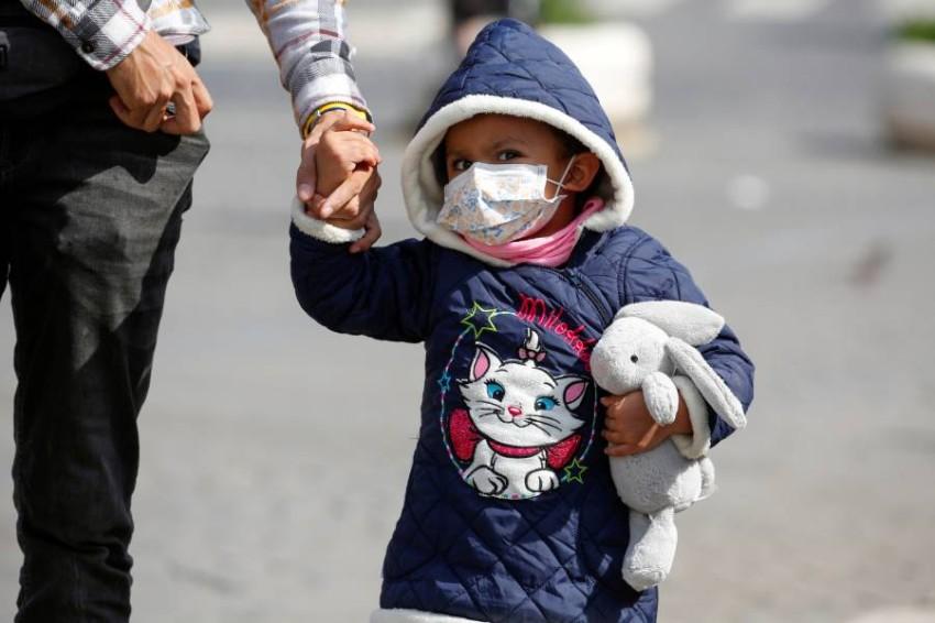 طفل يرتدي قناعاً واقياً في روما. (رويترز)