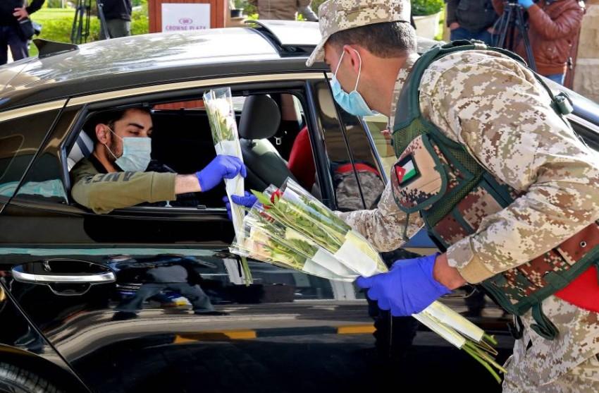 جندي أردني يوزع الورد على مغادري الحجر الصحي من منتجع البحر الميت - رويترز