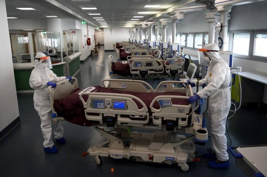 موظفو الرعاية الصحية يجهِّزون الأَسِرَّة في وحدة العناية المركزة في إيطاليا - رويترز