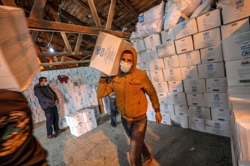 عمال فلسطينيون ينقلون مساعدات غذائية من الأنروا. (أي بي أيه)