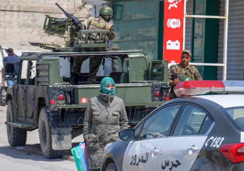 سيدة تونسية تسير بجوار جنود تابعين للجيش في نقطة أمنية. (أ ف ب)