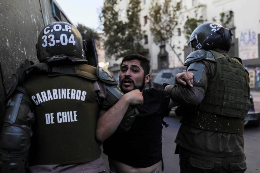 الأمن يلقي القبض على محتج في تشيلي. (رويترز)