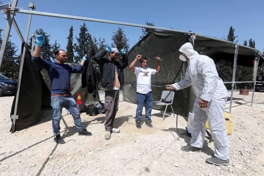 فلسطيني يرش العمال القادمين من إسرائيل بالمطهرات. (أي بي أيه)