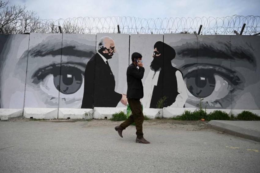 رجل يمر أمام لوحة في كابول تصور المبعوث الأمريكي لأفغانستان زلماي خليل زاد والزعيم السياسي لطالبان الملا عبد الغني باردار اللذين وقعا اتفاق الدوحة.