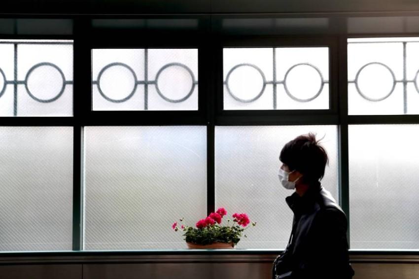 شخص يرتدي قناعاً واقياً في طوكيو. (أ ف ب)