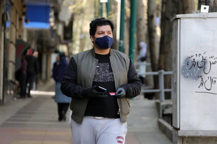 شخص يرتدي قناعاً واقياً في طهران. (أ ف ب)