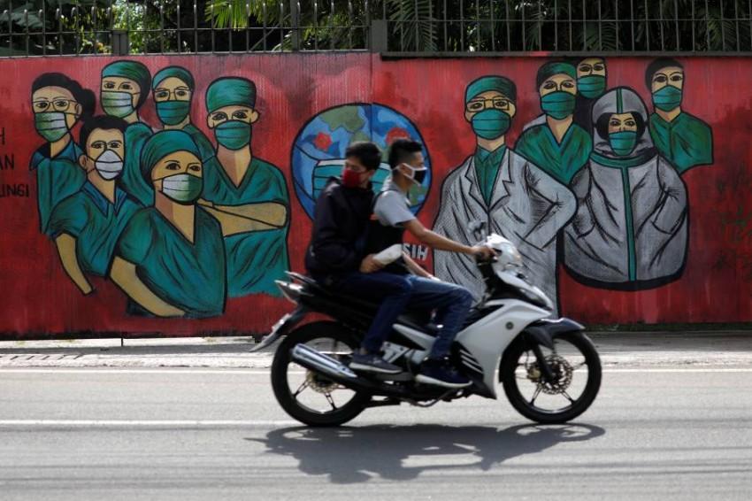 شخصان على متن دراجة نارية في إندونيسيا. (رويترز)