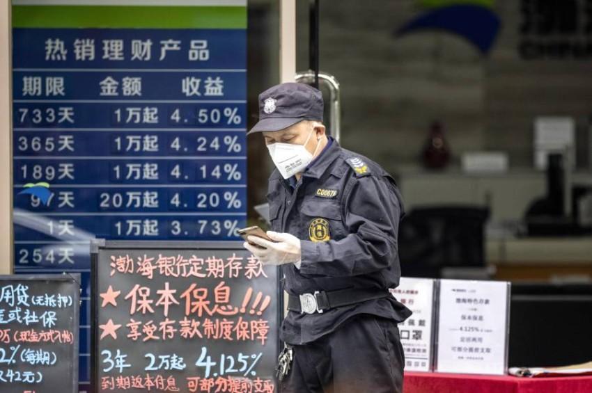 حارس أمن يرتدي قناعاً واقياً في الصين. (إي بي أيه)