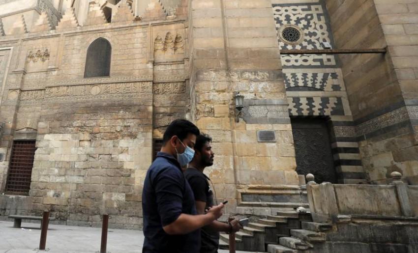 شخصان يسيران بشارع المعز لدين الله الفاطمي بالقاهرة. (رويترز)