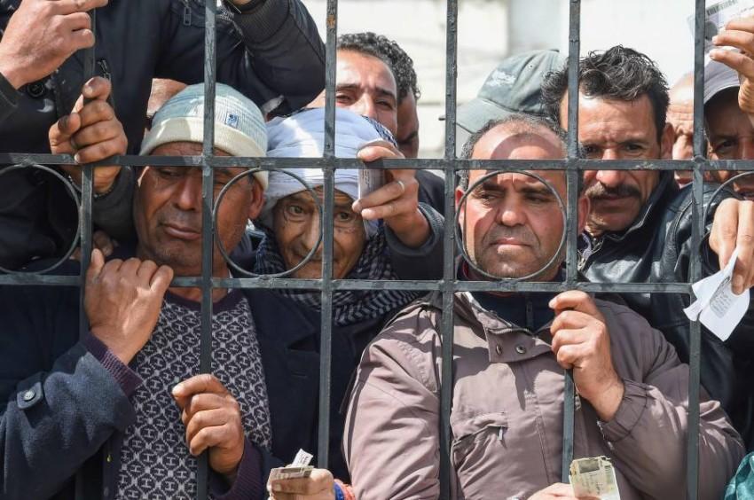 تونسيون ينتظرون صرف الإعانات من الحكومة. (أ ف ب)