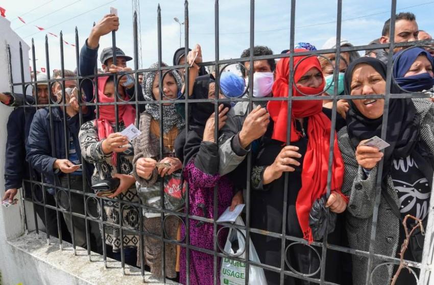 نساء تونسيات ينتظرن صرف الإعانات من الحكومة. (أ ف ب)