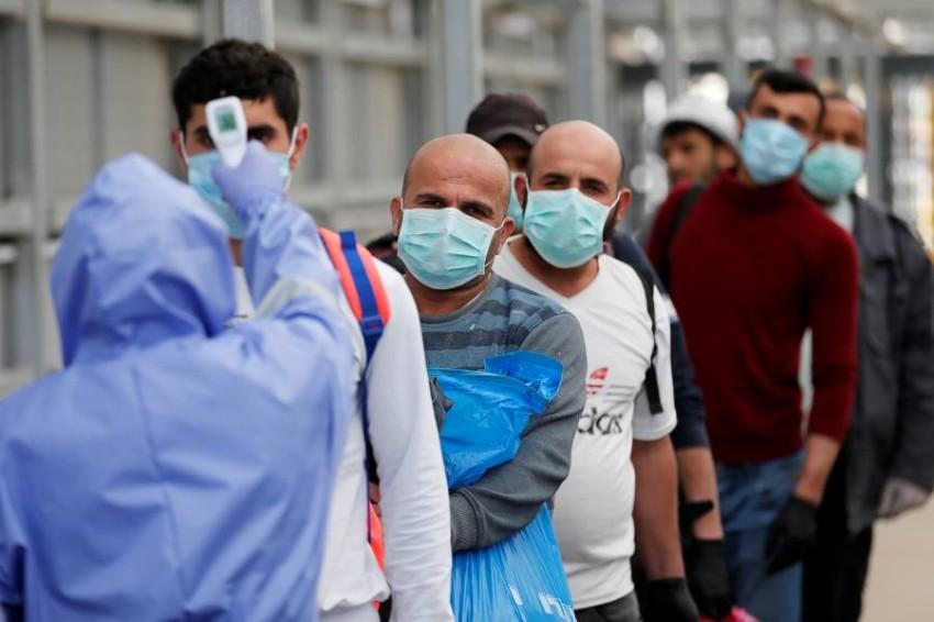 فحوص طبية للعمال الفلسطينيين العائدين للأراضي المحتلة. (رويترز)