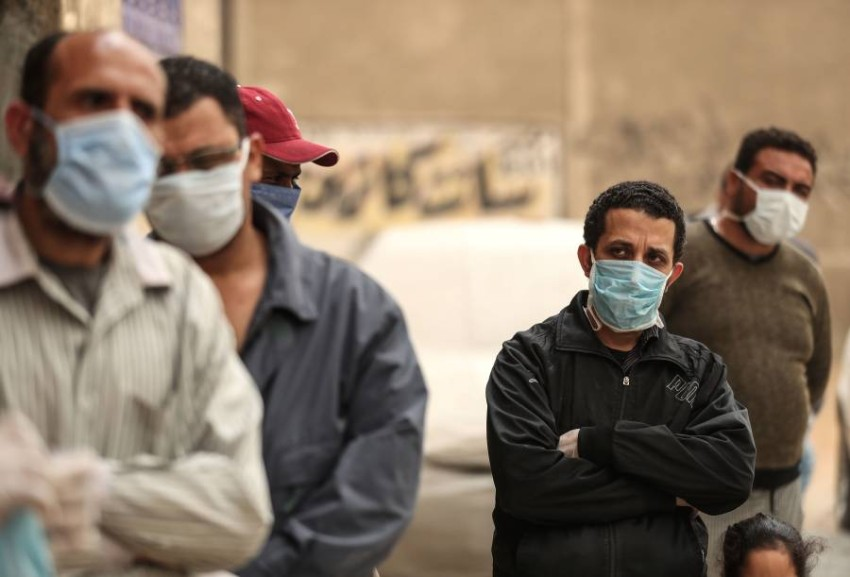 مصريون ينتظرون خارج إحدى المؤسسات الخيرية. (أ ف ب)