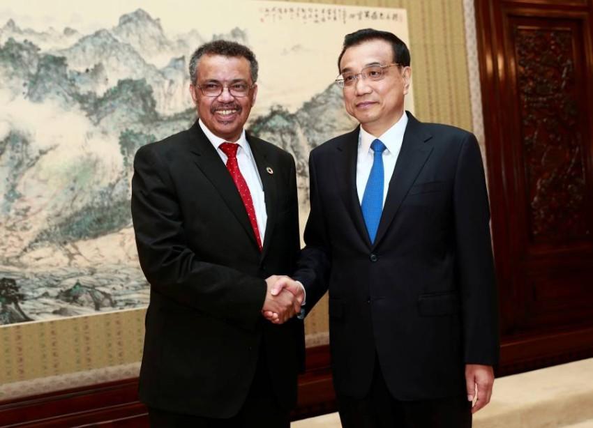 مدير منظمة الصحة العالمية مع رئيس الوزراء الصيني - رويترز