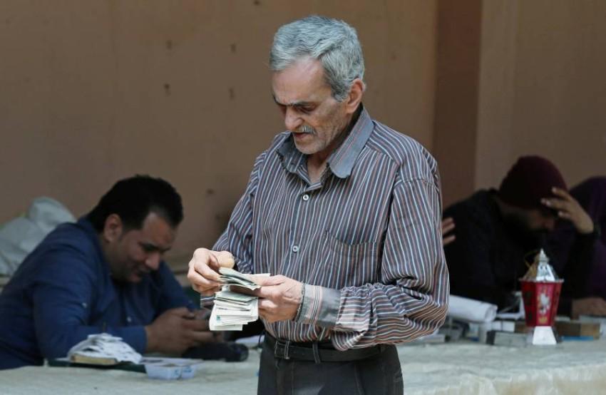 متقاعد مصري بعد الحصول على راتبه من مدرسة لمنع التزاحم. (رويترز)