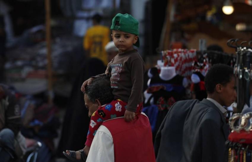 طفل يمني على كتفي أبيه في أحد أسواق صنعاء وسط المخاوف من تفشي كورونا. (إي بي أيه)