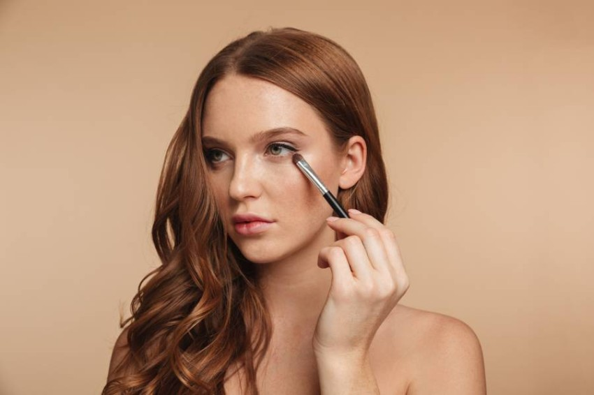 Beauty portrait of mystery smiling ginger woman with long hair looking away while applying cosmetics with brush for eyeshadow over cream background