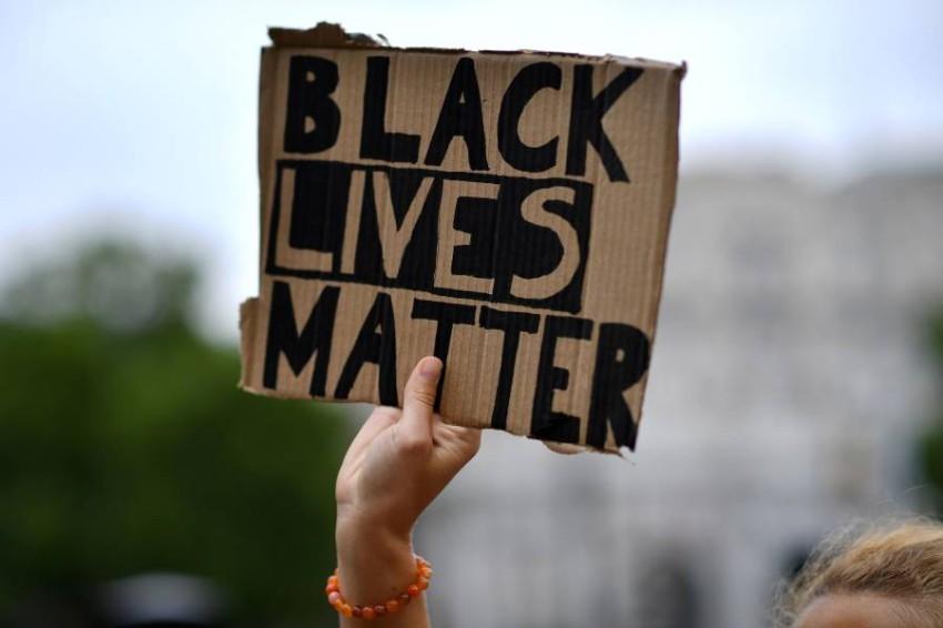 محتجة ترفع لافتة مدون عليها «حياة السود مهمة». (أ ف ب)
