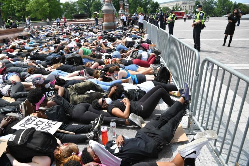 محتجون يرقدون على الأرض قرب مبنى الكونغرس الأمريكي. (أ ف ب)