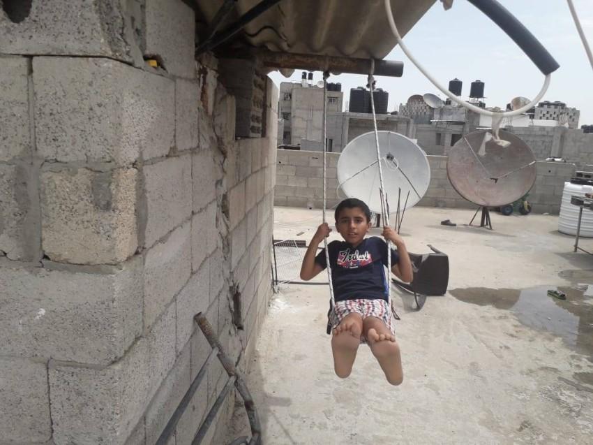 الطفل محمد يلعب على أرجوحته بعد انتهاء عمله في الحديقة. (الرؤية)