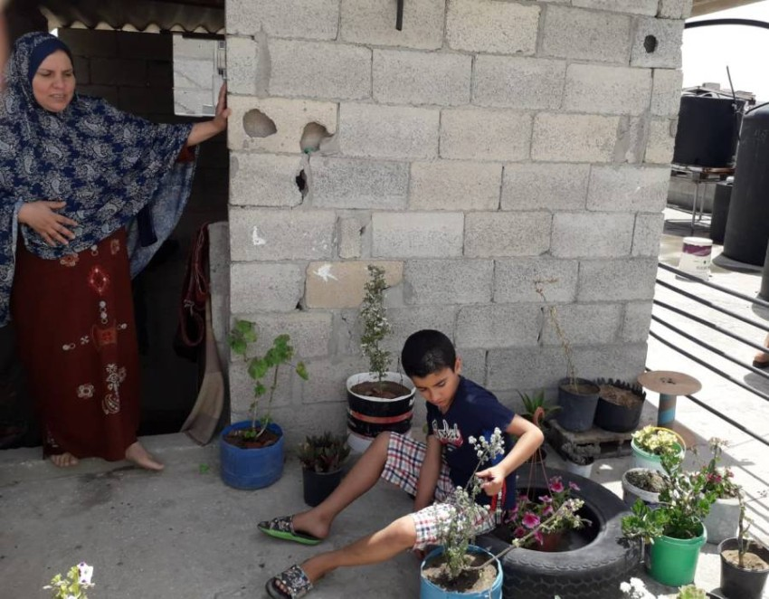 الطفل محمد يجلس وسط حديقته مع متابعة والدته له. (الرؤية)