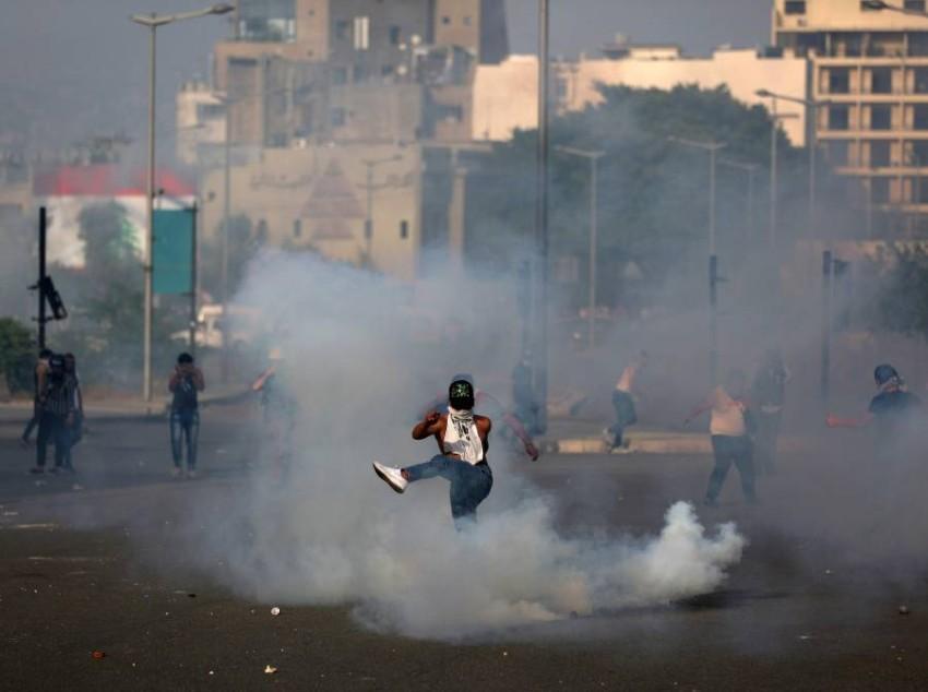 المتظاهرون يردون قنابل الغاز التي يطلقها الجيش عليهم.(أ ف ب)