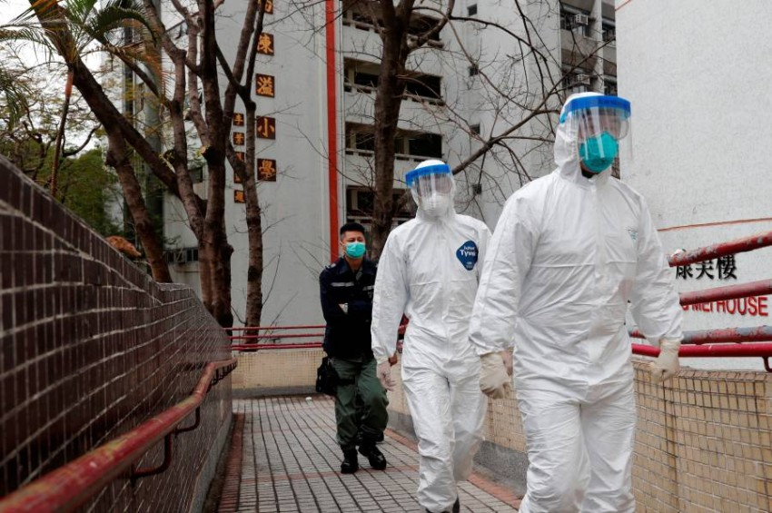 Health workers in protective gears walk as they evacuate residents from a public housing building, following the outbreak of the novel coronavirus, outside Hong Mei House, at Cheung Hong Estate in Hong Kong, China February 11, 2020. REUTERS/Tyrone Siu